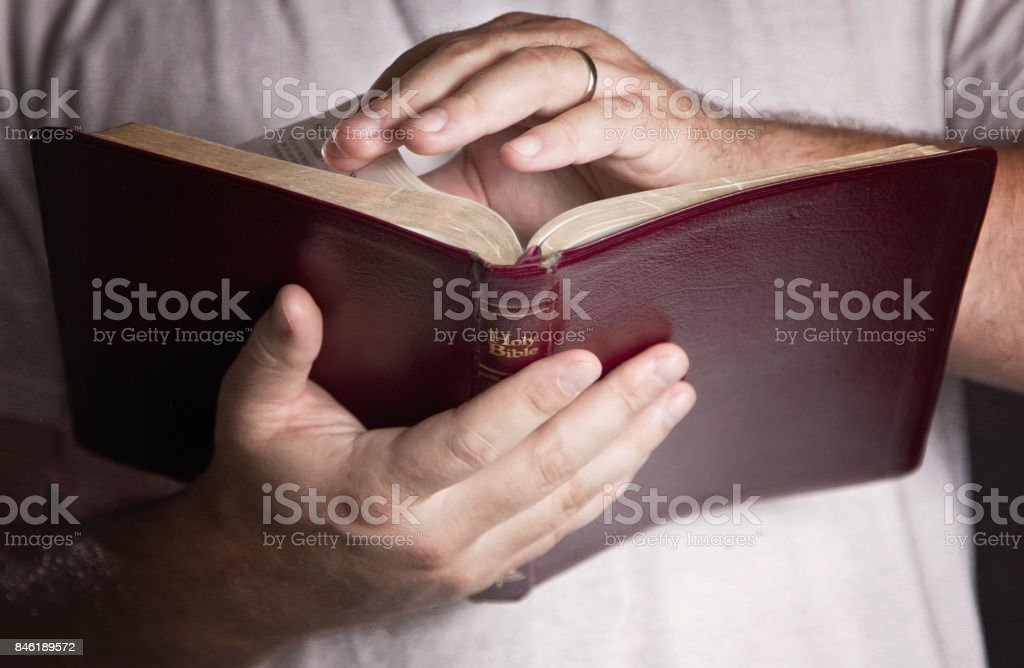 Man in a White T-Shirt Reading the Bible stock photo