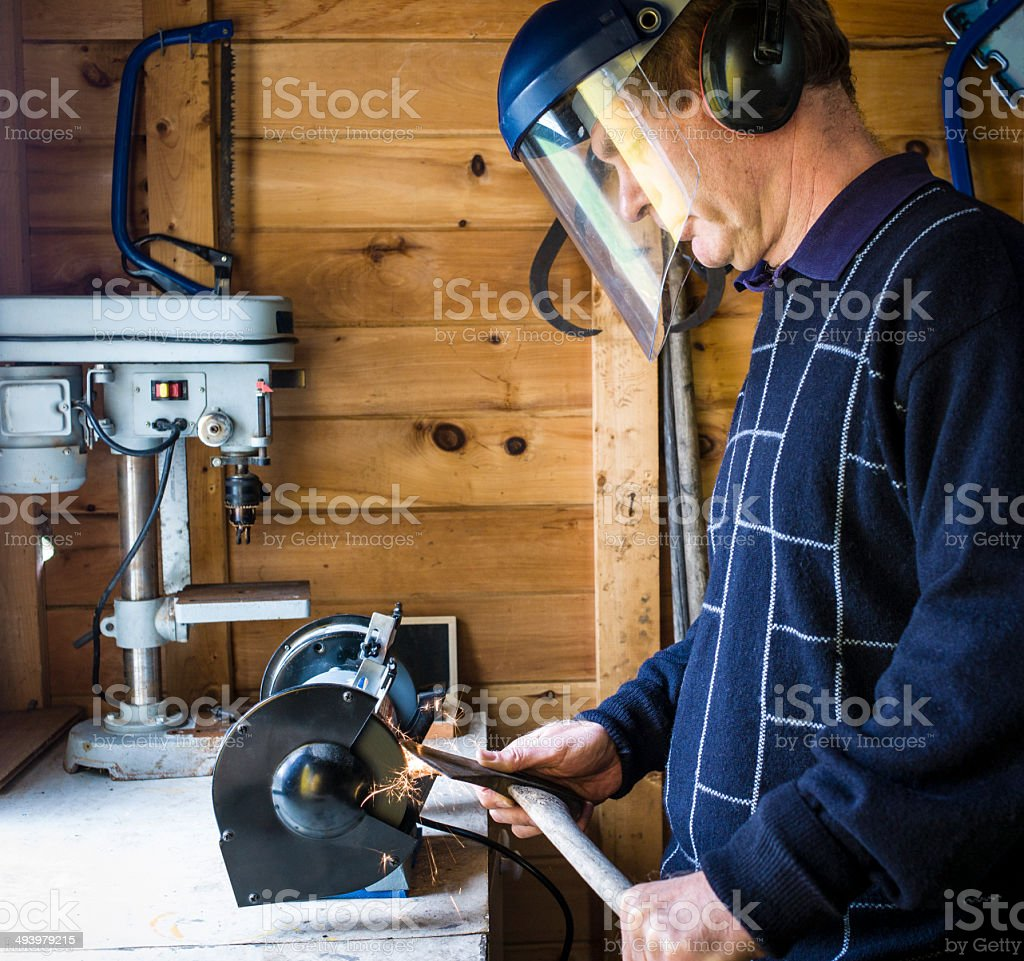 Man in a Workshop Sharpening an Axe. stock photo