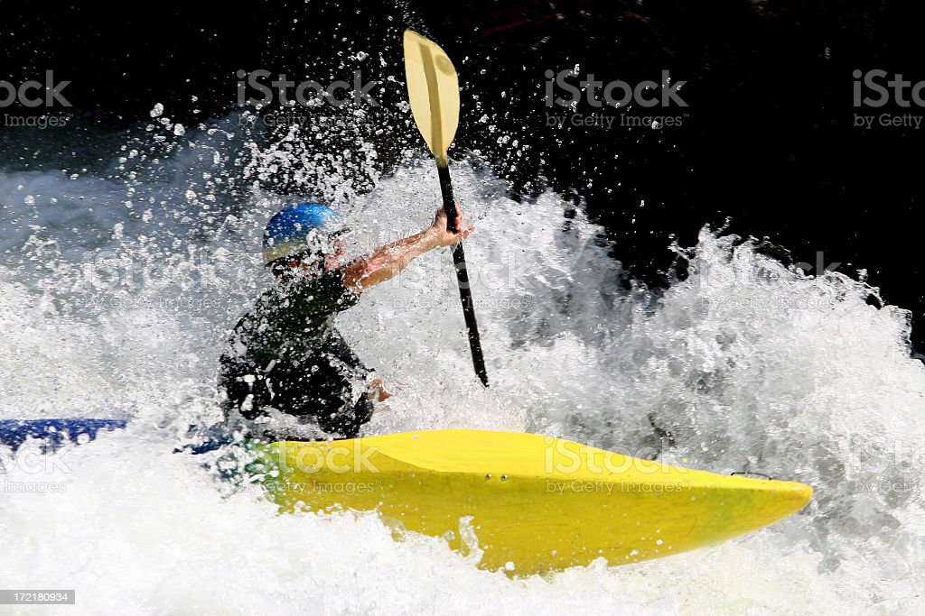 Man in a yellow kayak going down the river stock photo
