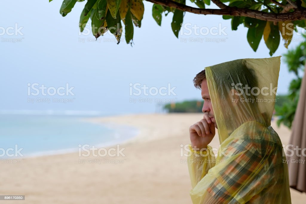 Man in a yellow raincoat on tropical seashore during rain. stock photo