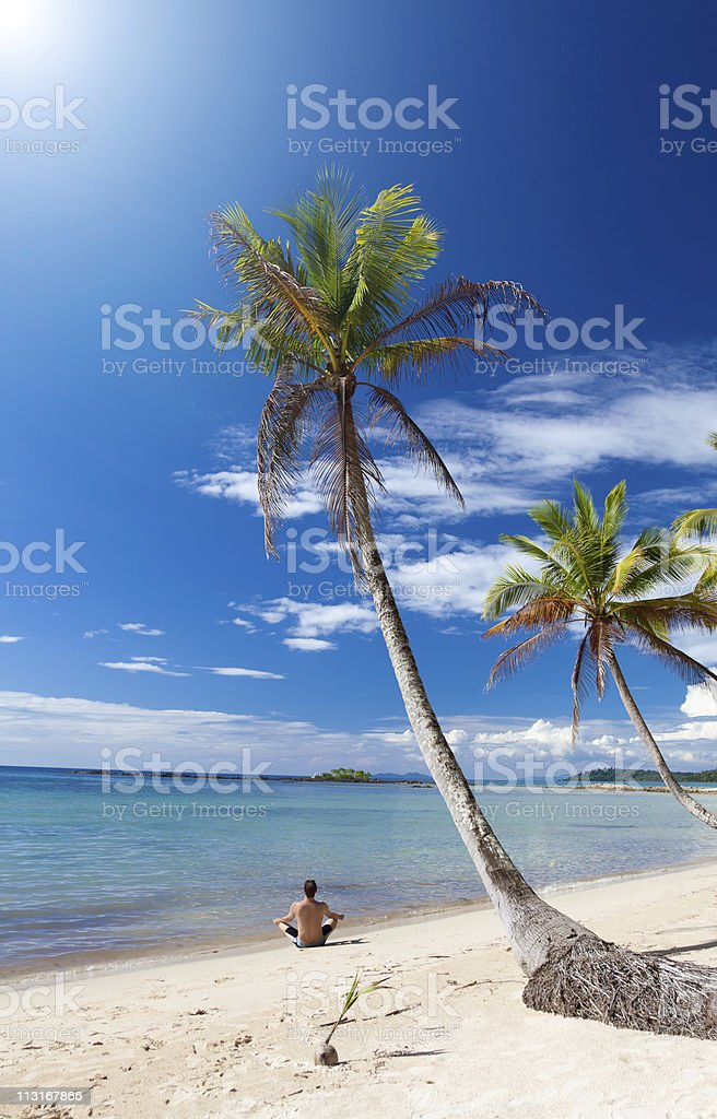 Man in a yoga posture relaxes under palm trees royalty-free stock photo