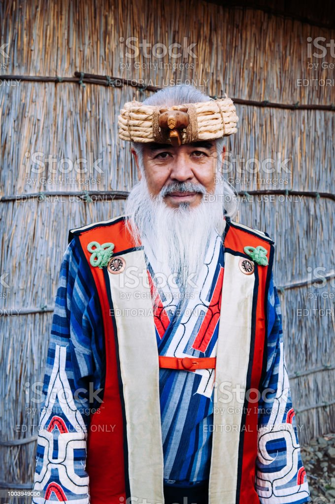A man in Ainu tradition tribal costume at Shiraoi Ainu Museum. The indigenous people of northern Japan. stock photo