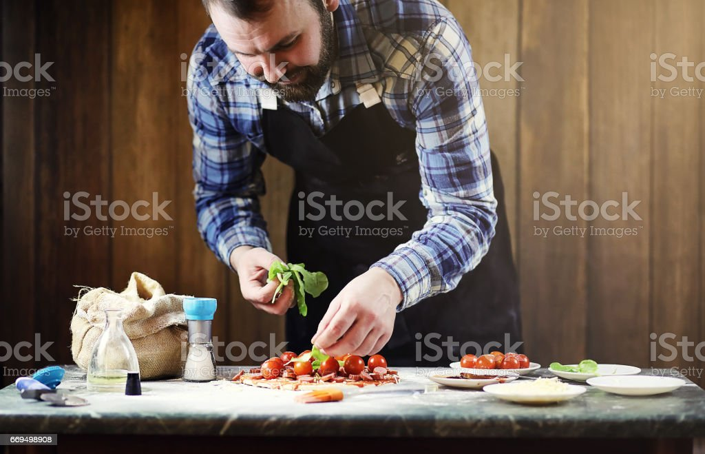 man in an apron preparing a pizza, knead the dough and puts ingr stock photo