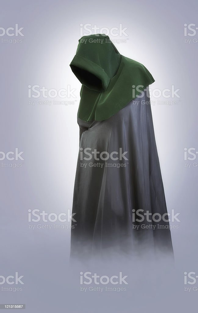 Man in an medieval hood and cloak into the fog stock photo