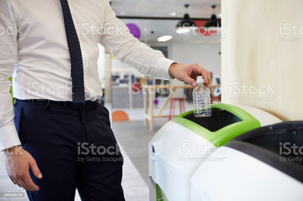 Man in an office recycling plastic bottle, close up stock photo