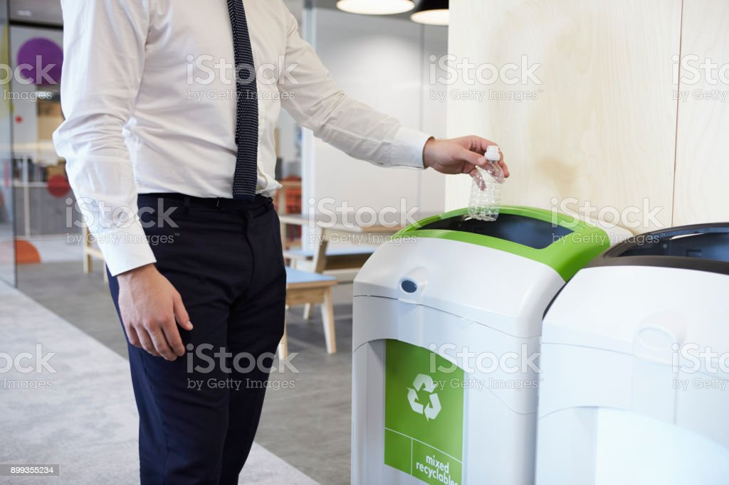 Man in an office throwing plastic bottle into recycling bin royalty-free stock photo