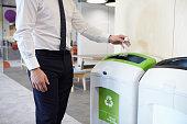 istock Man in an office throwing plastic bottle into recycling bin 899355234