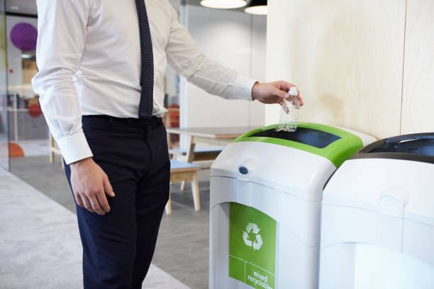 man in an office throwing plastic bottle into recycling bin - riciclaggio foto e immagini stock