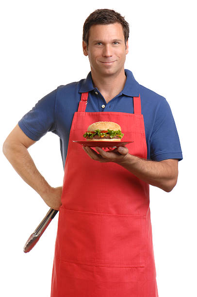mann in schürze hält hamburger isoliert auf weißem hintergrund - grillschürze stock-fotos und bilder
