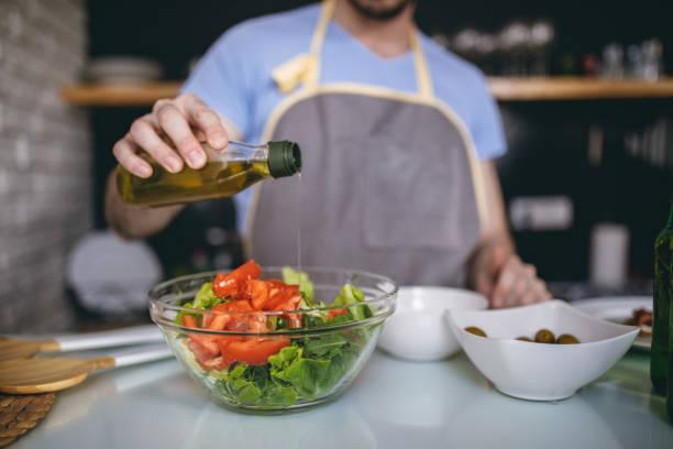 Man in apron preparing salad in kitchen stock photo