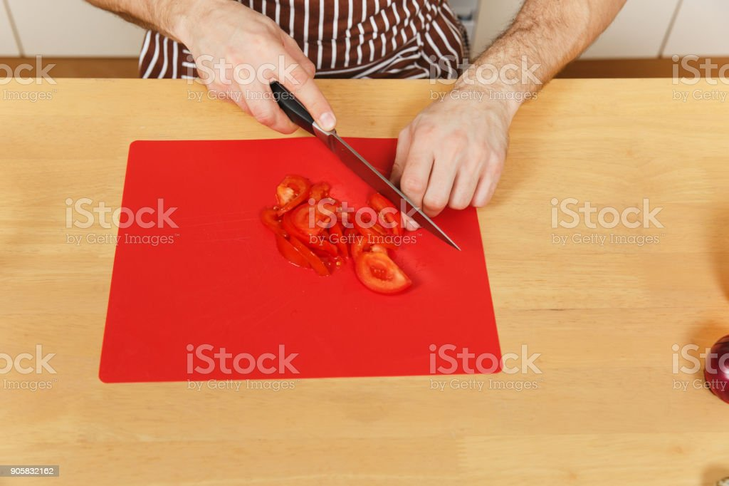 Man in apron sitting at table, cuts tomato and vegetables for salad with knife on red board in light kitchen. Dieting concept. Cooking at home. Prepare food. Top view. Copy space for advertisement. stock photo