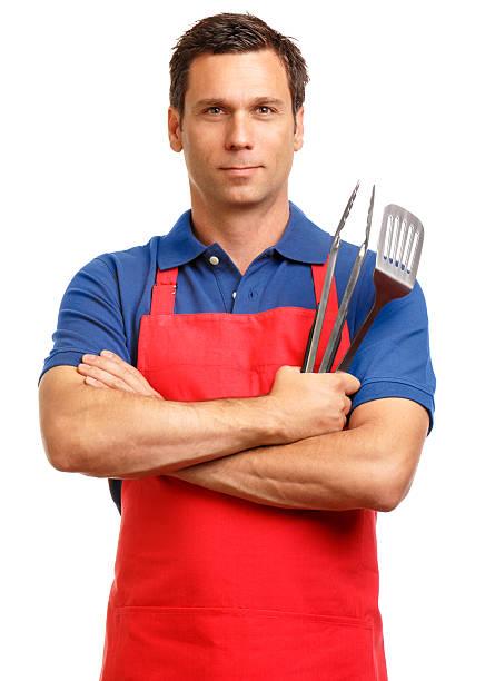 man in apron with cooking utensils on white - grillschürze stock-fotos und bilder