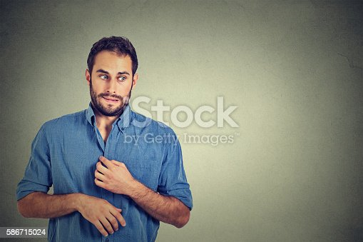 Portrait young man opening shirt to vent, it's hot, unpleasant, awkward situation, playing nervously with hands. Embarrassment. Isolated gray background. Negative emotions facial expression feeling