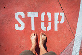 istock A man in bare feet stops at a stop mark painted on the ground. 1272687872