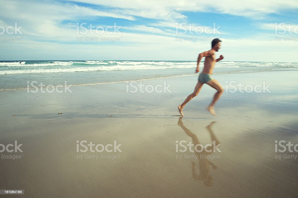 Man in Bathing Suit Runs Across Bright Tropical Beach stock photo