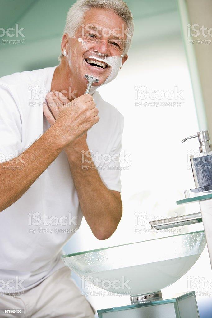 Man in bathroom shaving royalty free stockfoto
