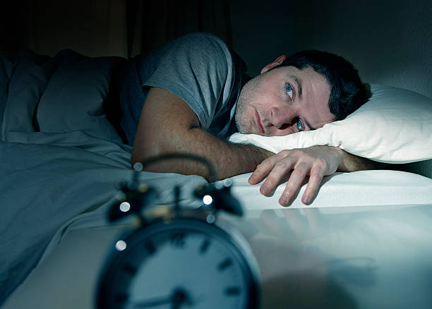 man in bed eyes opened suffering insomnia and sleep disorder stock photo