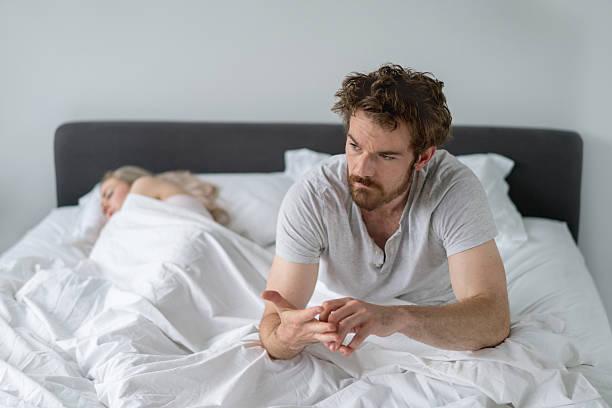 man in bed looking upset - liebeskummer englisch stock-fotos und bilder