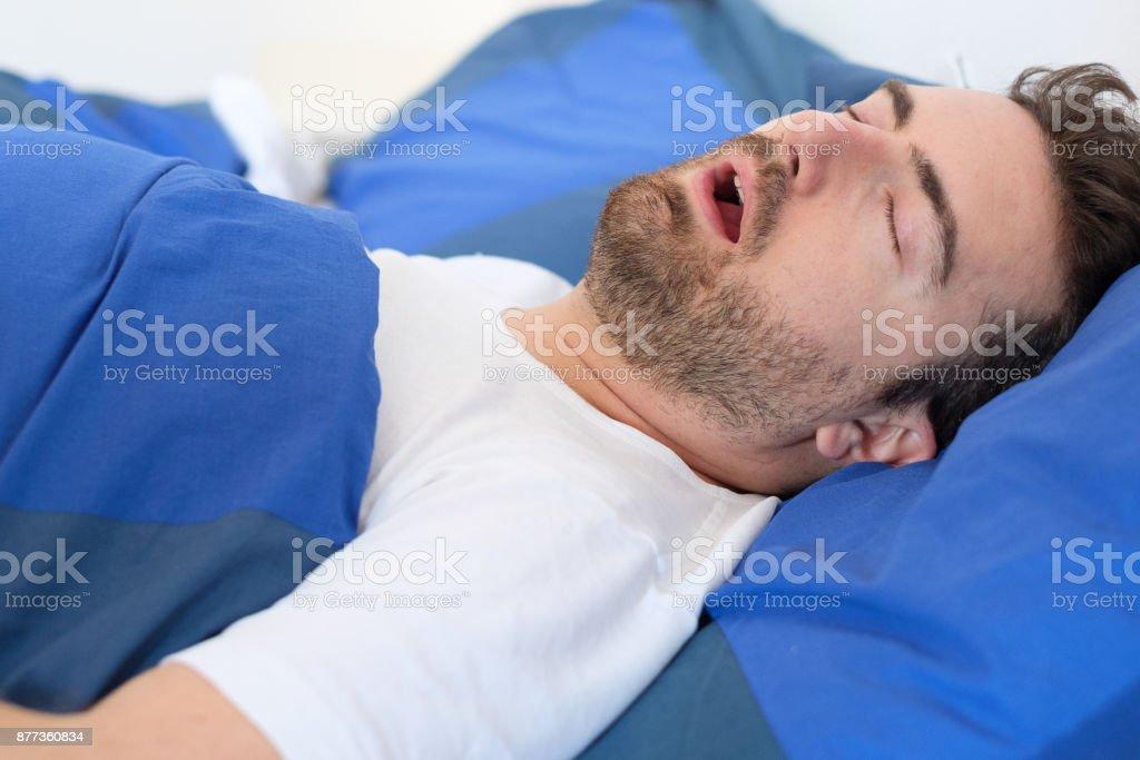 Mann im Bett für Schlaf-Apnoe-Syndrom leiden – Foto