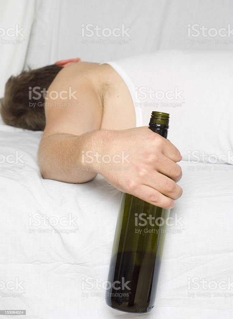 Man in bed with a wine bottle stock photo