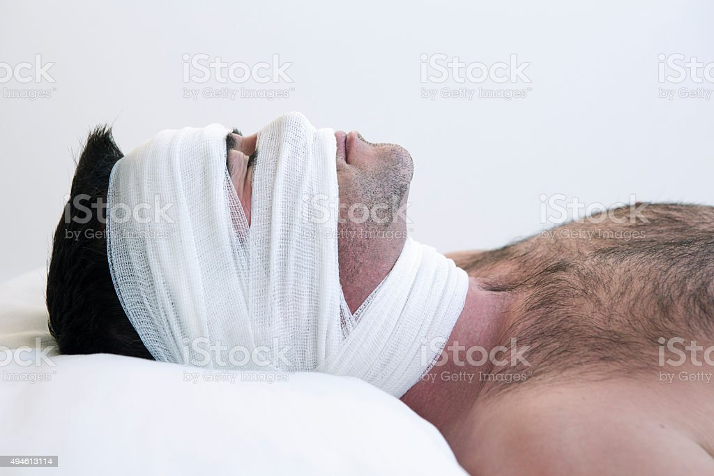 man in bed with bandages stock photo