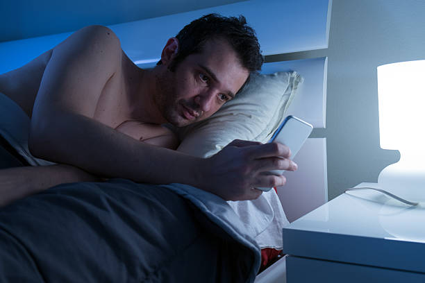 Man in bed with mobile phone - foto stock