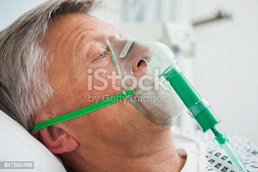 Man in bed with oxygen mask in hospital