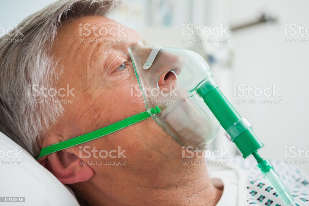 Man in bed with oxygen mask stock photo