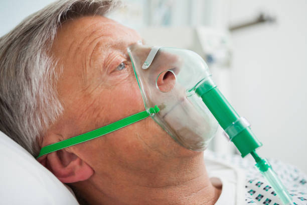 Man in bed with oxygen mask Man in bed with oxygen mask in hospital oxygen mask stock pictures, royalty-free photos & images
