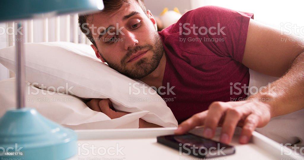 Homem na cama acordado por rádio no telefone celular - foto de acervo