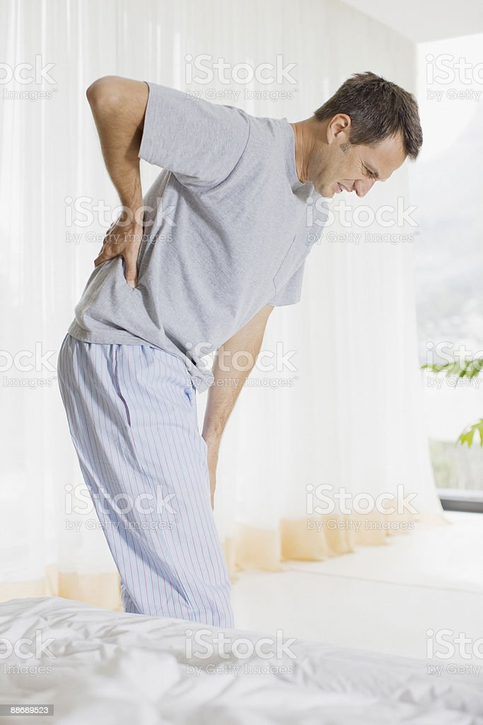 Man in bedroom with backache stock photo