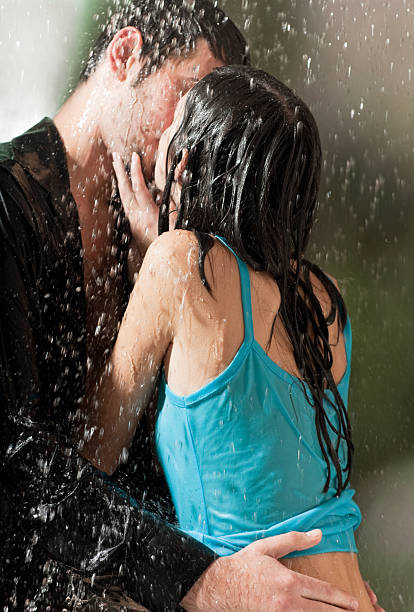 Man in black and woman in blue kissing in the rain stock photo