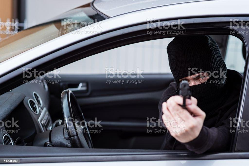 Man in black balaclava with handgun driving a car. stock photo