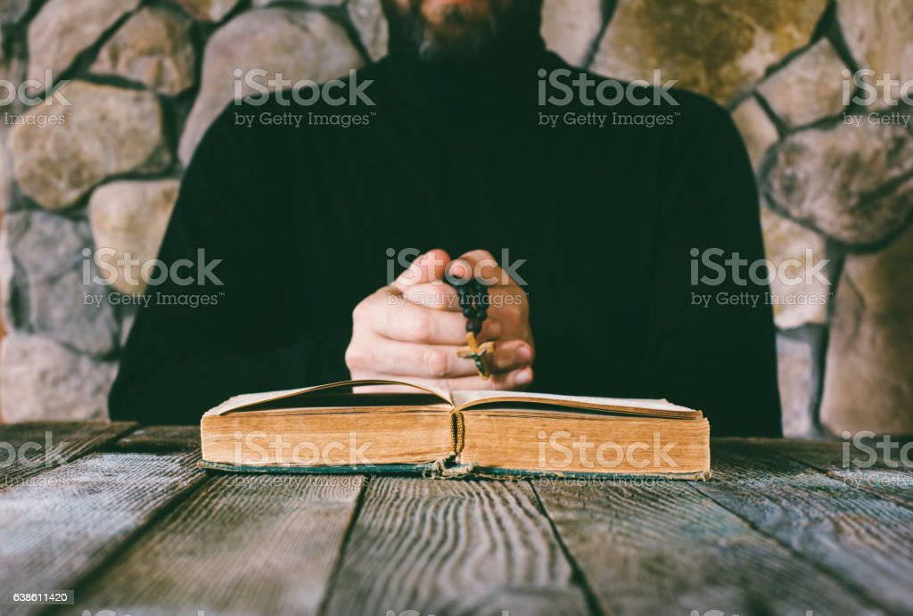 man in black clothes with a prayer beads in hand stock photo