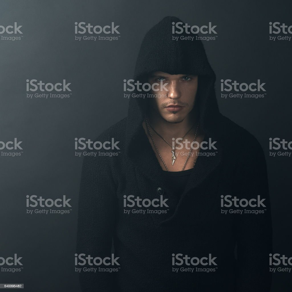 man in black hoodie looking confidently stock photo
