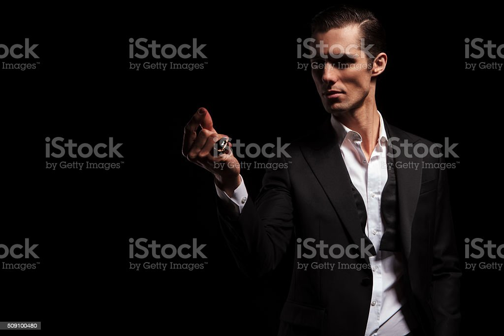 man in black jacket posing in dark while snapping fingers stock photo