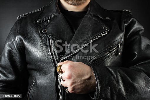 Photo of a man in black leather biker jacket and rings closeup view on black background.
