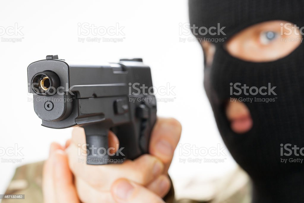 Man in black mask holding gun stock photo