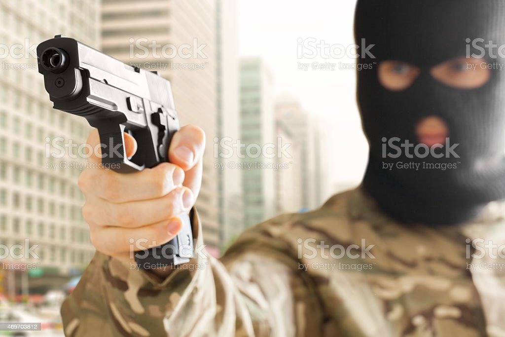 Man in black mask holding gun with city on background stock photo