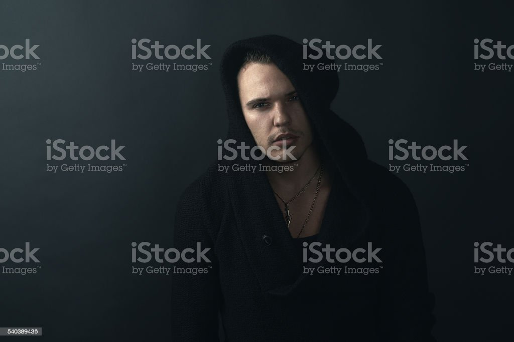 man in black robe looking confidently stock photo