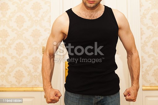 Young aggressive Caucasian man in black shirt clenches his fists menacingly, domestic violence concept
