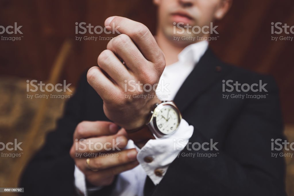 Man in black suit wear new watches. Luxury style stock photo