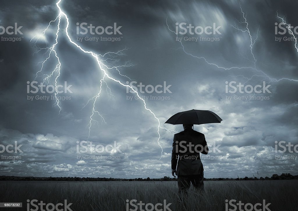 Man in black suit with a black umbrella in a storm stock photo