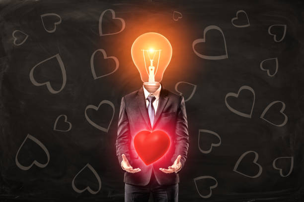 Man in black suit with light bulb instead head, levitating red glaring heart with his palms, standing against black background with heart pattern on it.