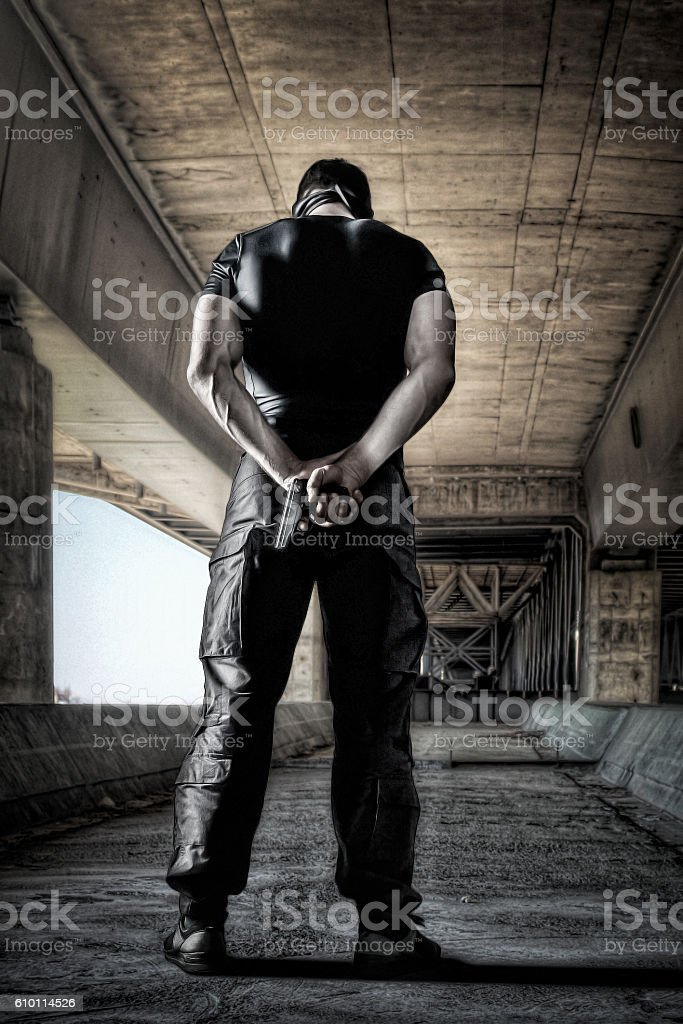 Man in black uniform and mask standing with gun stock photo