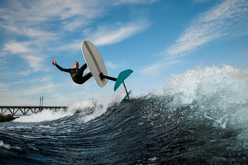 man in black wetsuit is vigorously jumping over the wave with foilboard