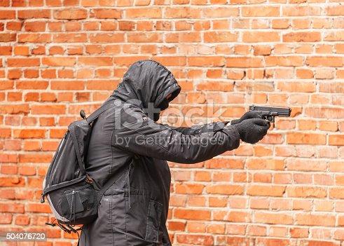 istock man in black with gun 504076720