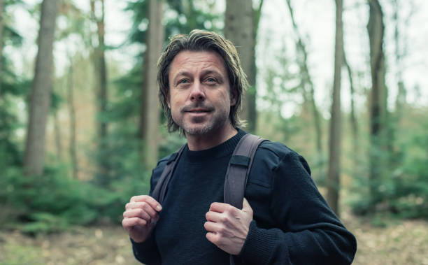 Man in black woolen sweater and backpack hiking in forest. stock photo