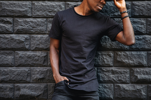 istock Man in blank black t-shirt standing against brick wall, cropped shot 1011172508