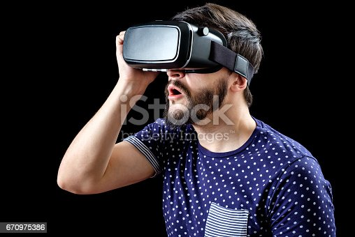 istock Man in blue dotted T-shirt wearing virtual reality 3d-headset isolated on black 670975386